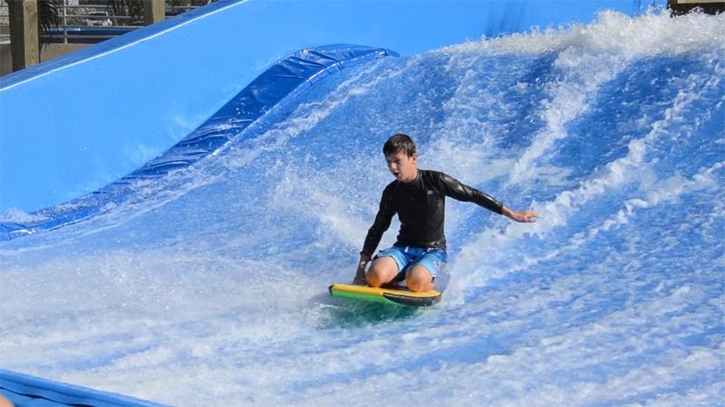 A boy riding a boogie board on FlowRider.