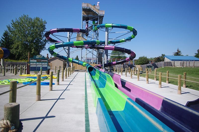 Two twisting water slides leading into a swimming pool.