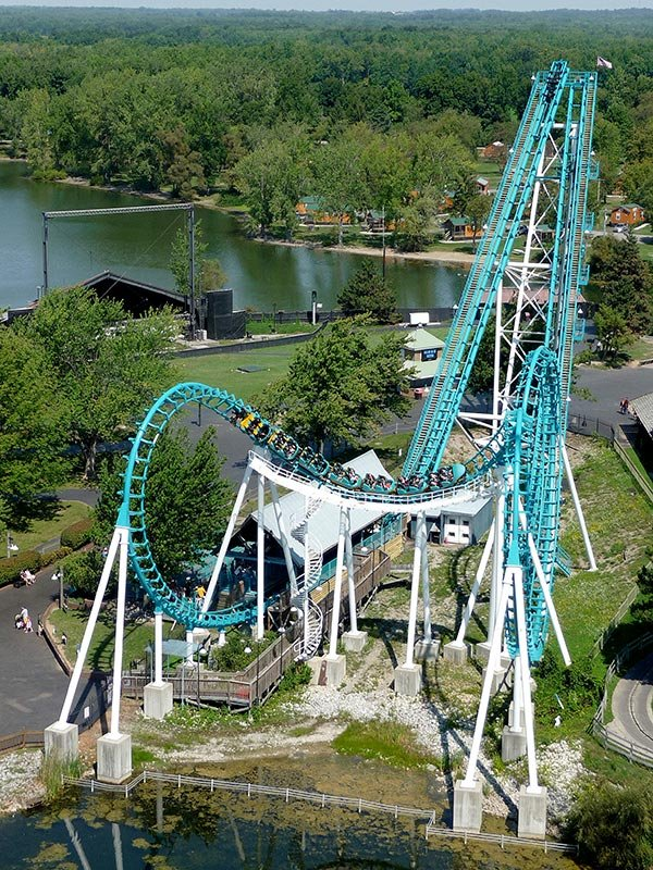 People riding a turquoise roller coaster.