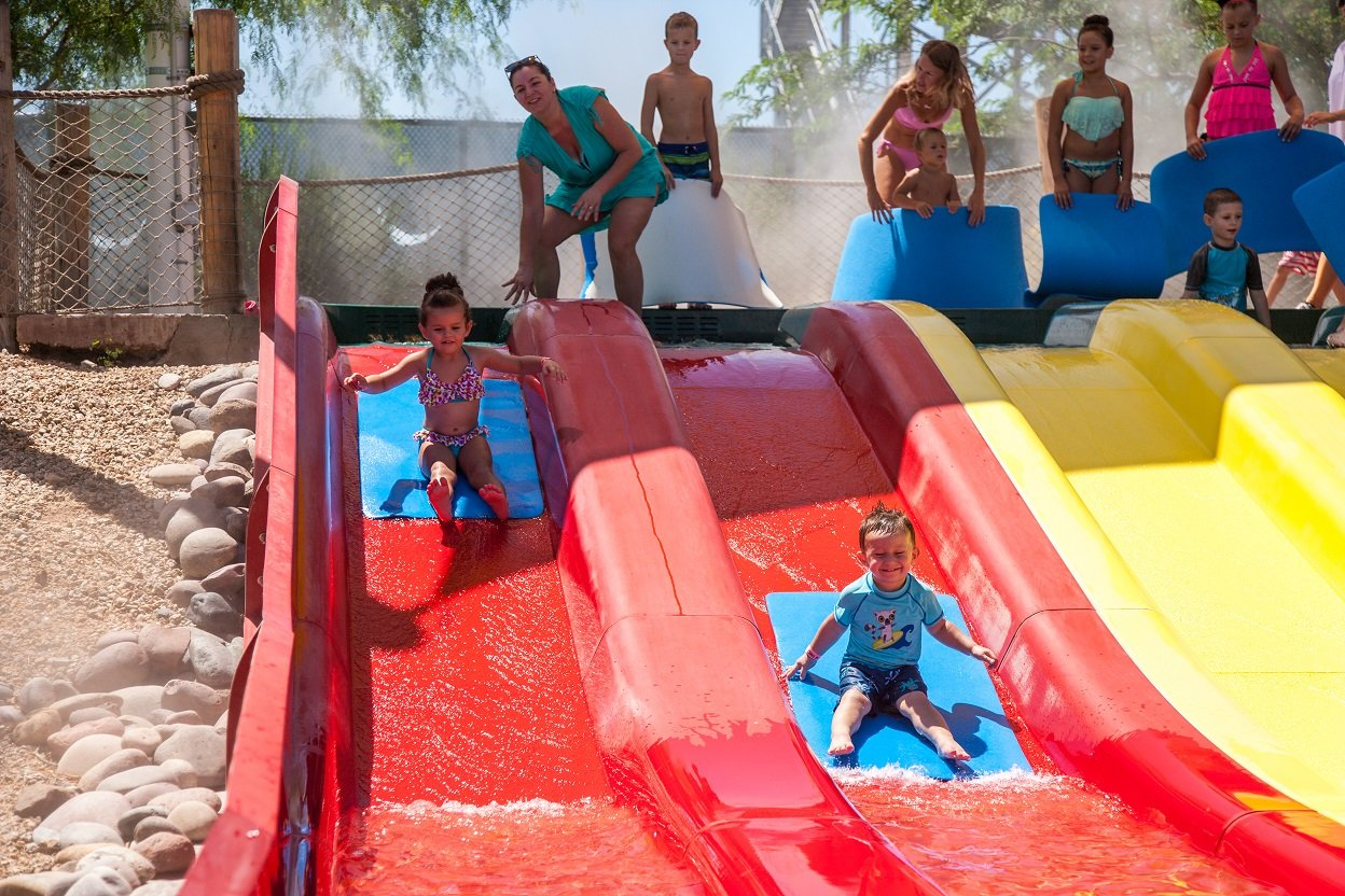 Two people riding down the slides at Coconut Bay.