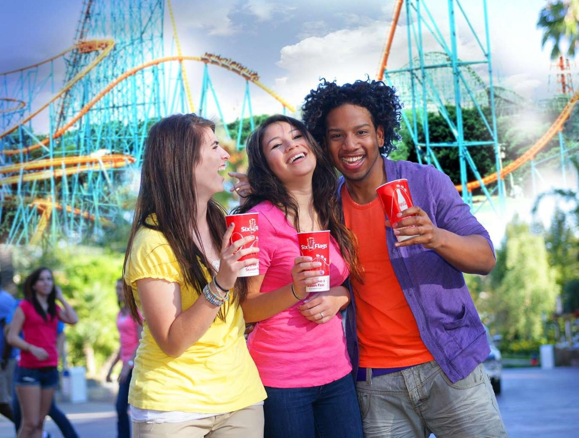 Group of friends smiling and laughing with roller coaster in the background