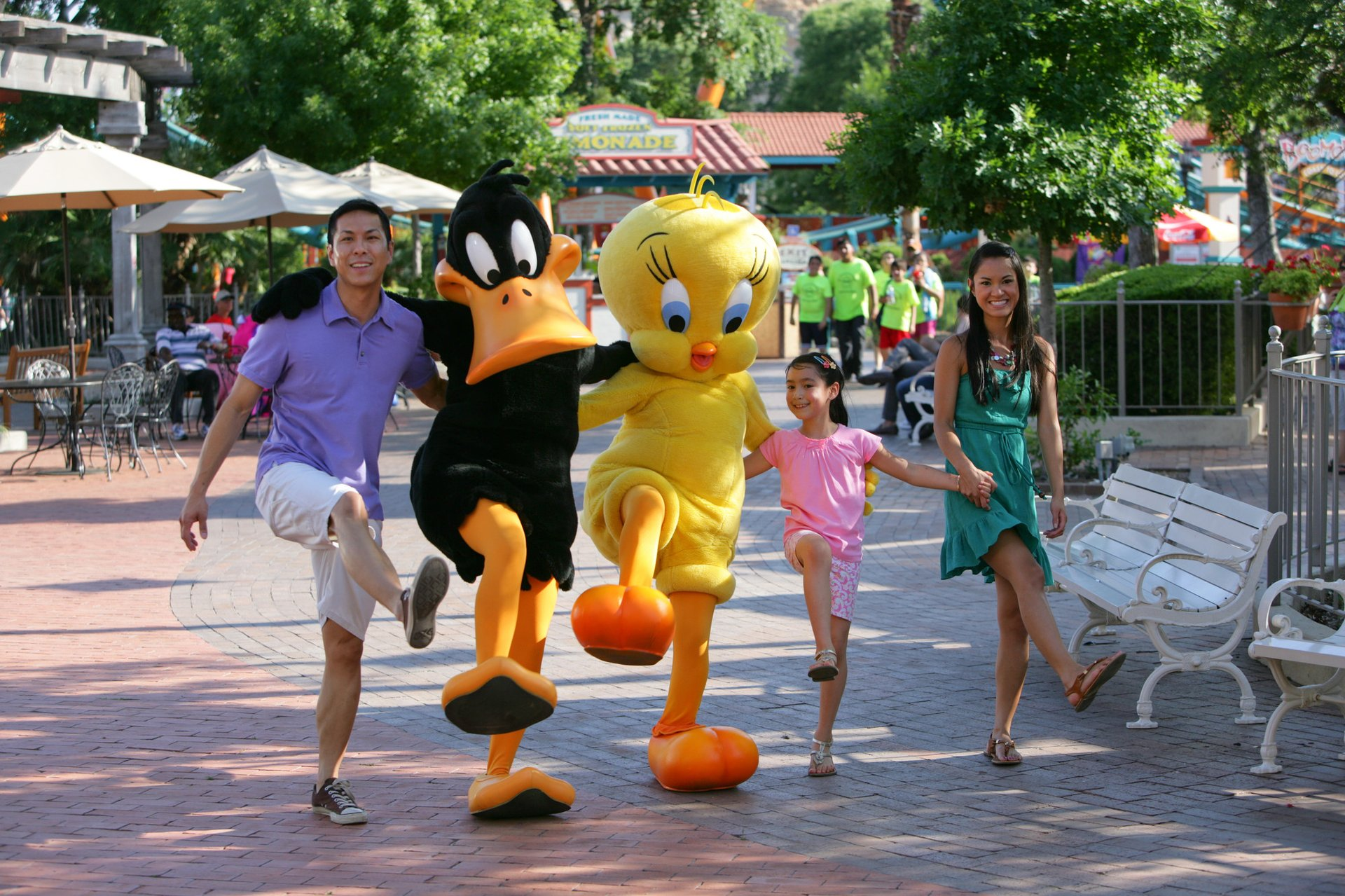 A family walking with characters at Six Flags theme park