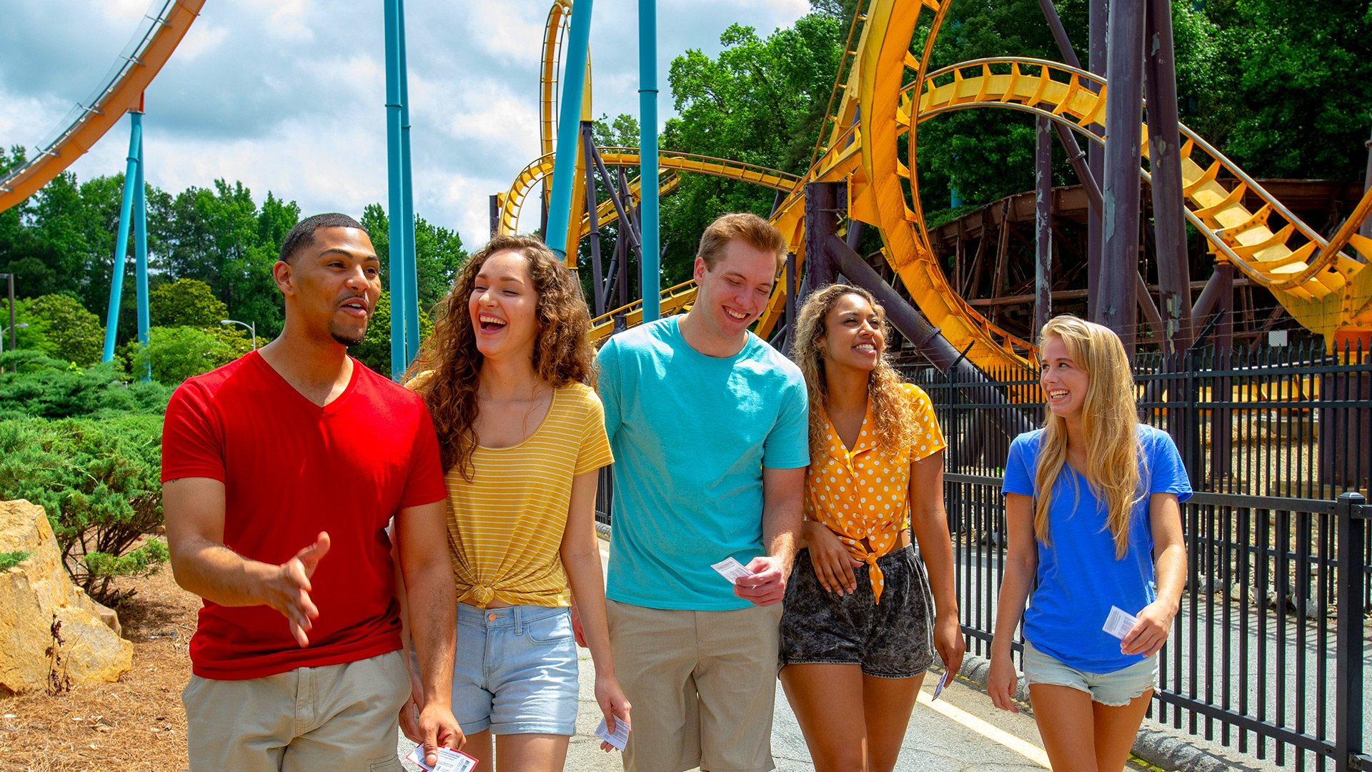 A group of people laughing and talking at Six Flags theme park