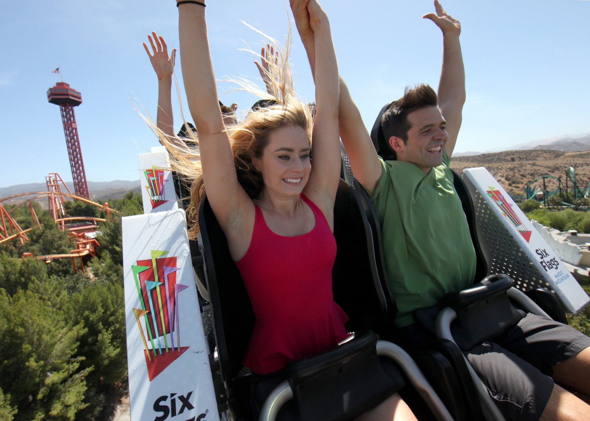 People on a roller coaster with their hands in the air