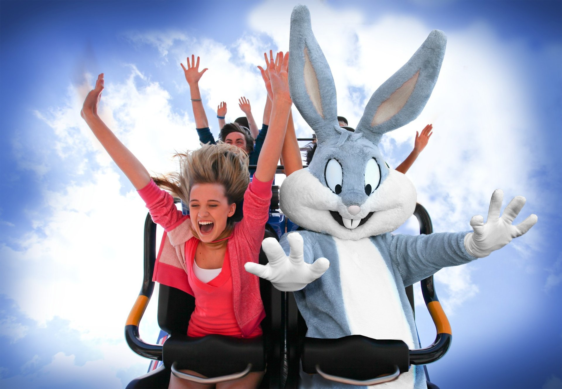 People and characters on a roller coaster with their hands in the air