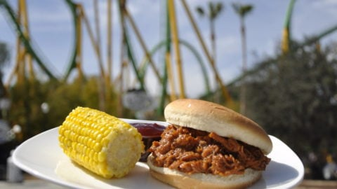 A BBQ brisket Sandwich with Corn on the Cob on a plate in front of The Riddler's Revenge