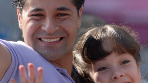 Father and daughter smiling and waving at camera on ride