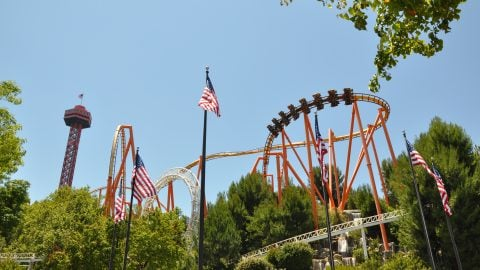 Six American flags flying at the park with a view of coasters at Six Flags