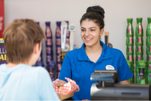Six Flags employee checking out guest at cash register