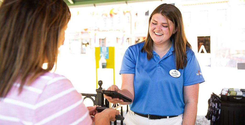 an employee smiling while helping a guest at six flags