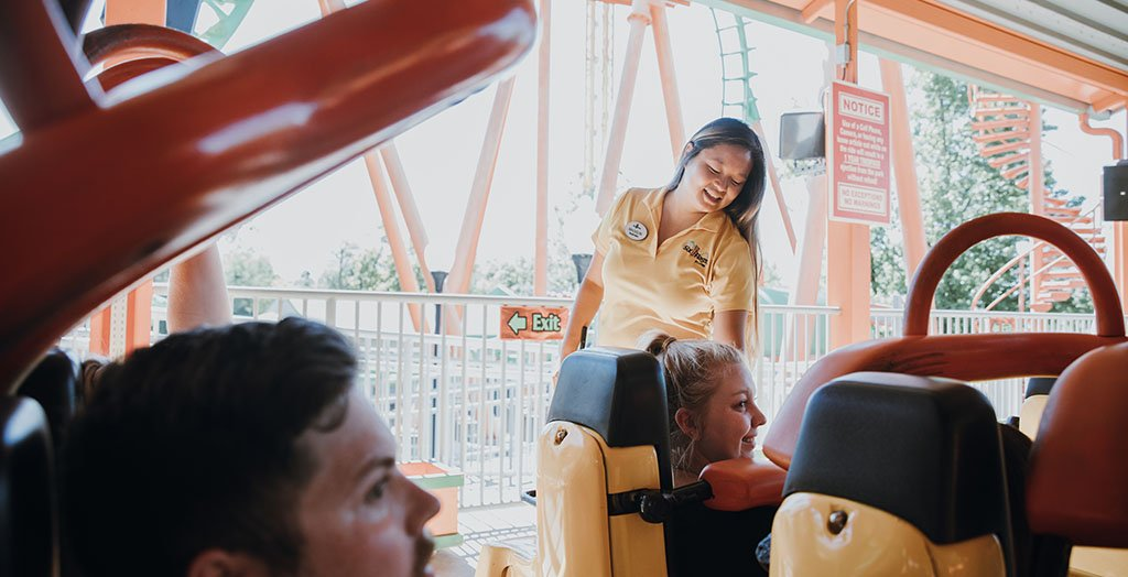 an employee smiling while helping guests onto a coaster at six flags
