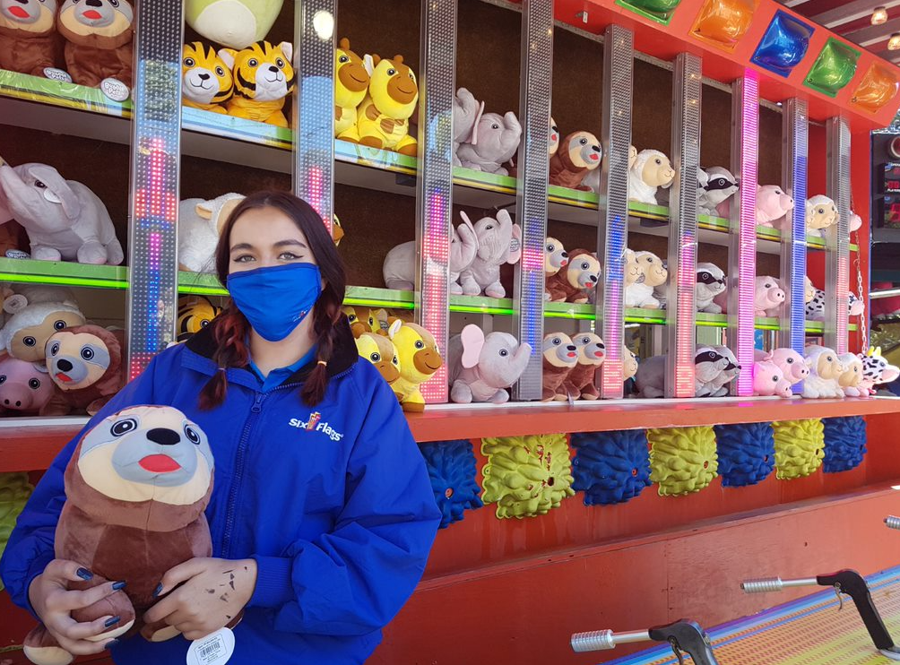 a masked employee holding a stuffed animal prize in a game at Six flags