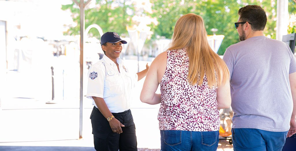 a security guard smiling while helping guests at six flags